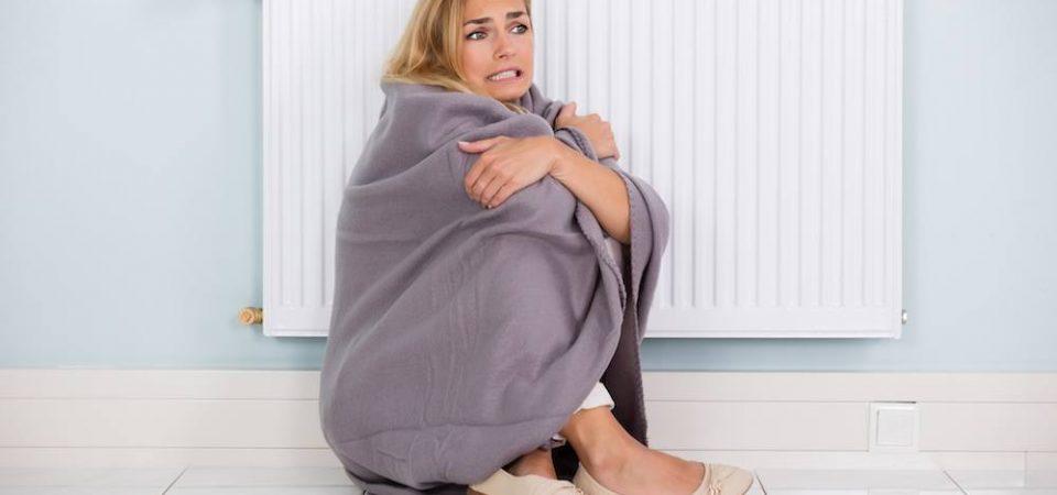 Vrouw die het koud heeft en zich tegen de radiator aanschurkt.