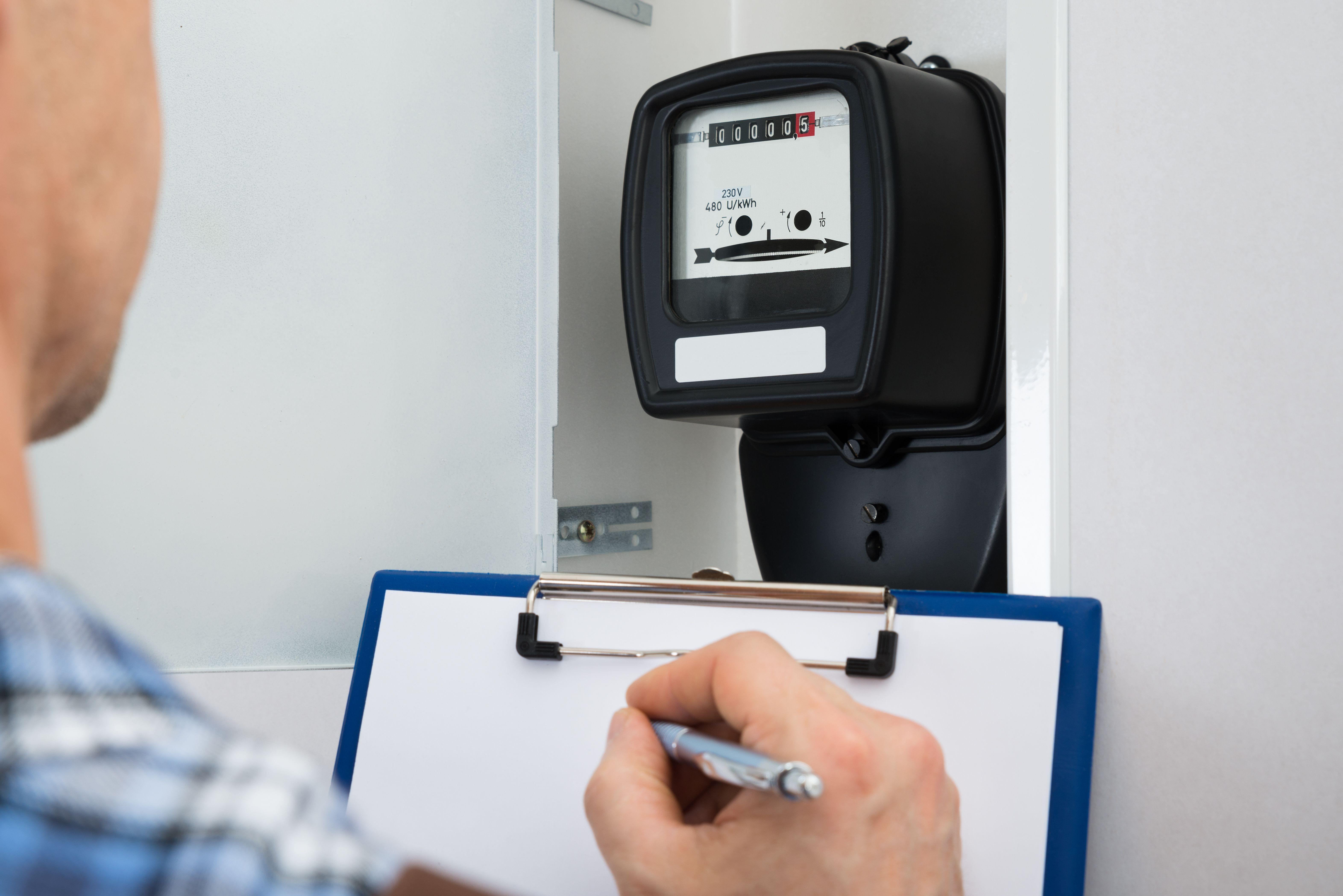 Een DNB technicus neemt de stand van de elektriciteitsmeter op -Energie-vergelijker